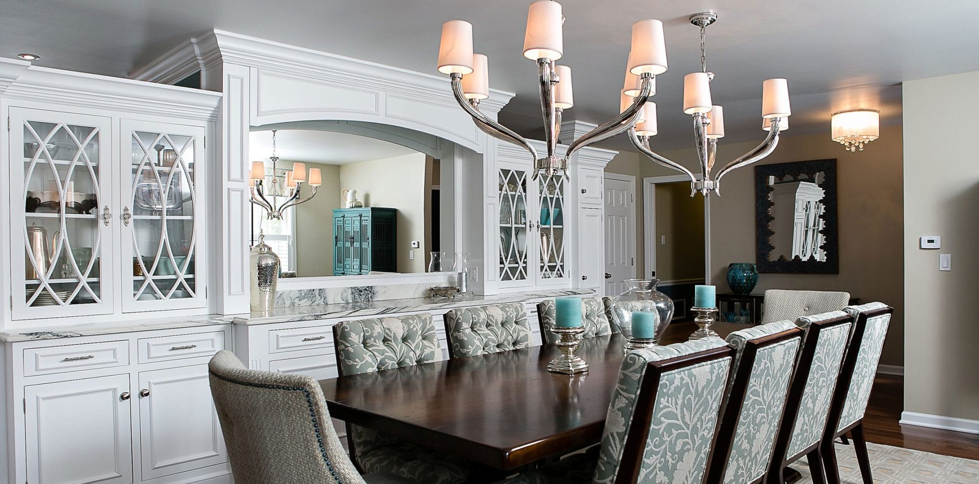 two chandeliers hang over large dining table with custom white marble buffet and storage