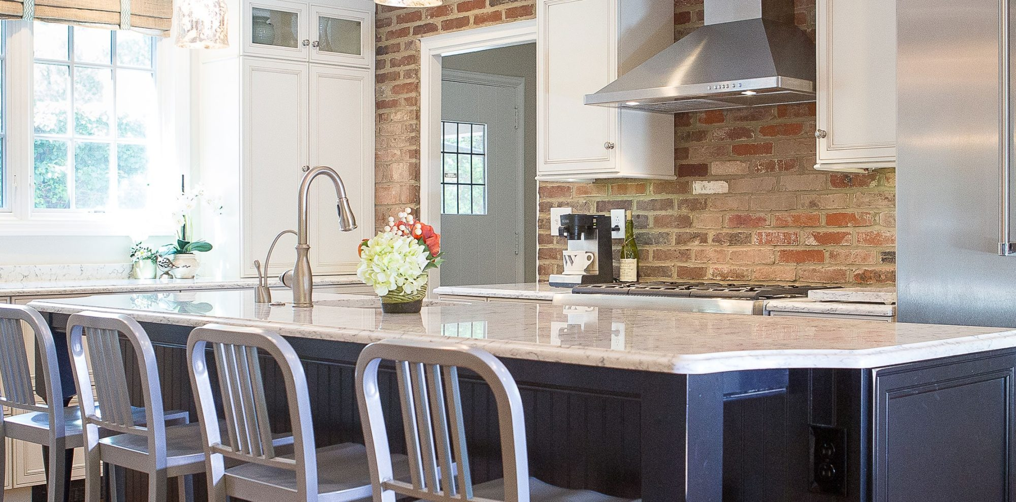 Warm marble counter tops meet brick wall in renovated kitchen