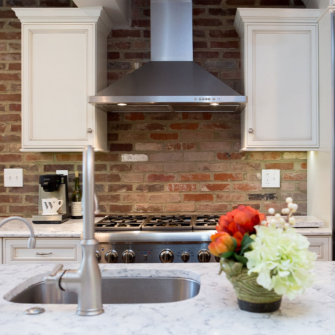 Existing brick wall warms renovated kitchen with white cabinets and marble countertops