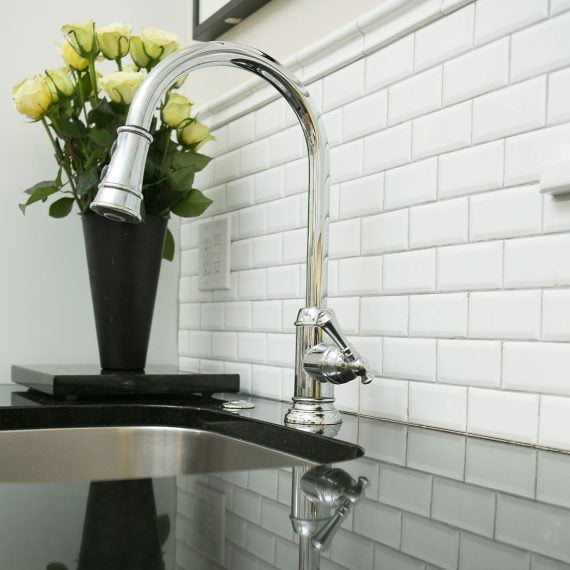 subway tile backsplash behind modern chrome faucet on black marble countertops in renovated kitchen