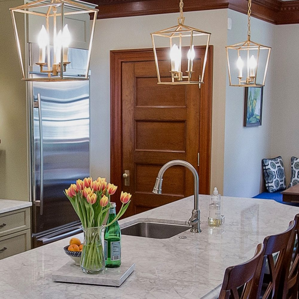 Brass lamp pendant lights over marble island in renovated kitchen