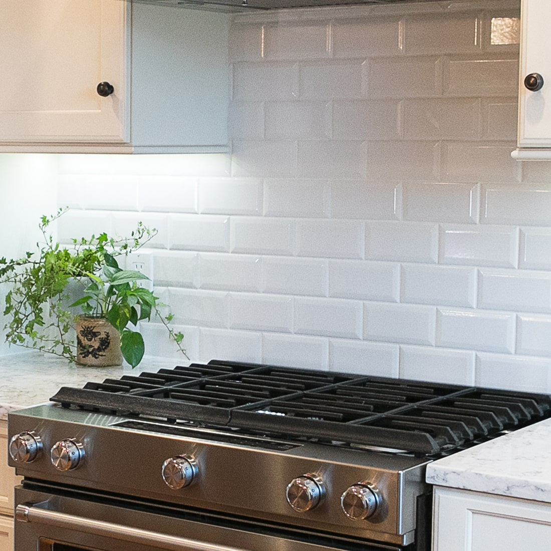 detail of modern stove range with white subway tile.