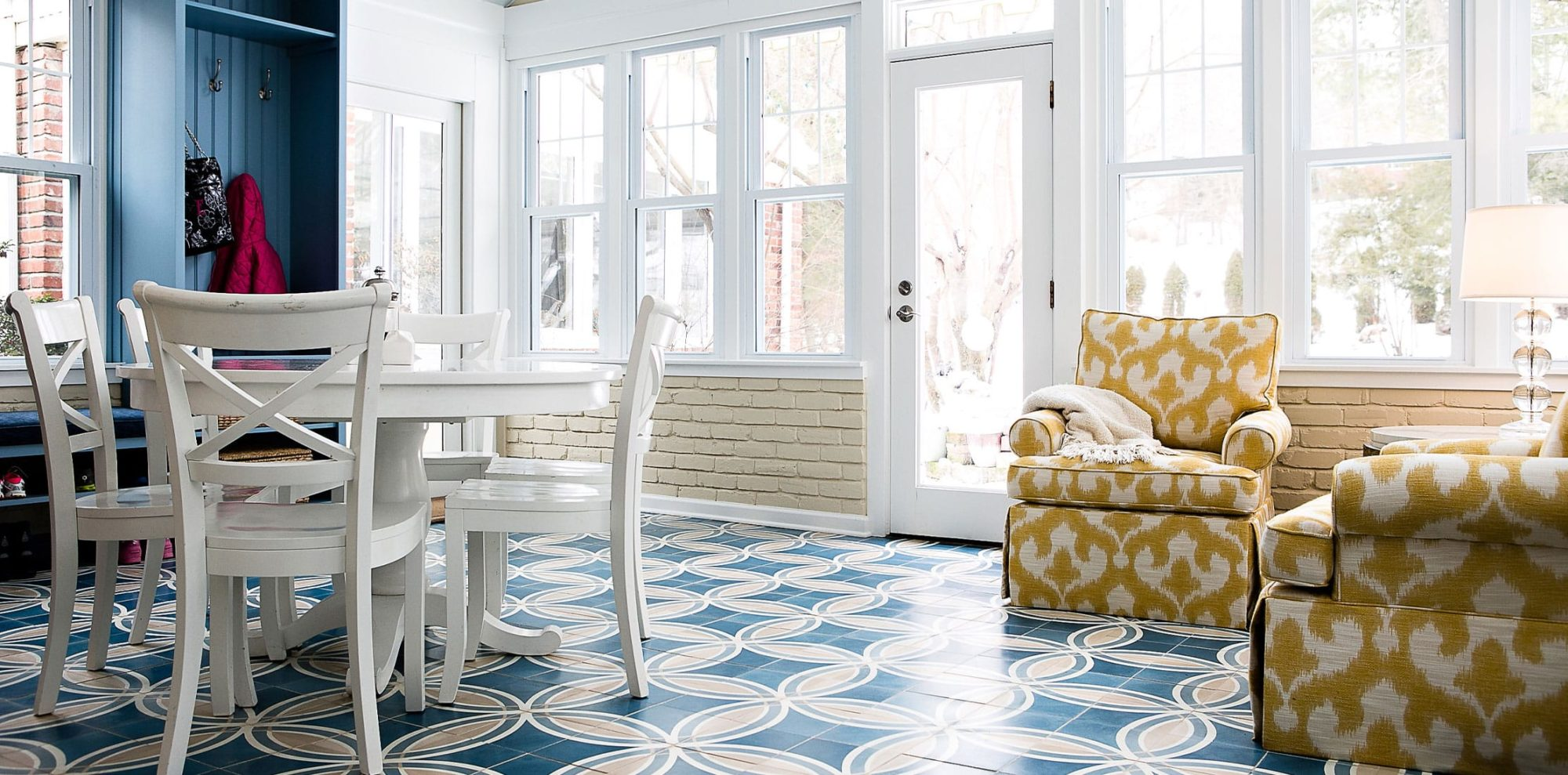 Wide angle of blue pattern tiles and bright yellow lounge chairs in sunroom