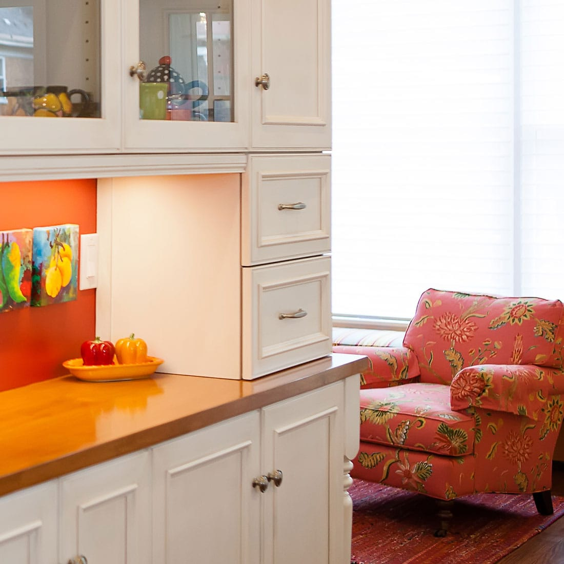 Bright color accents in white kitchen with bright lounge chair