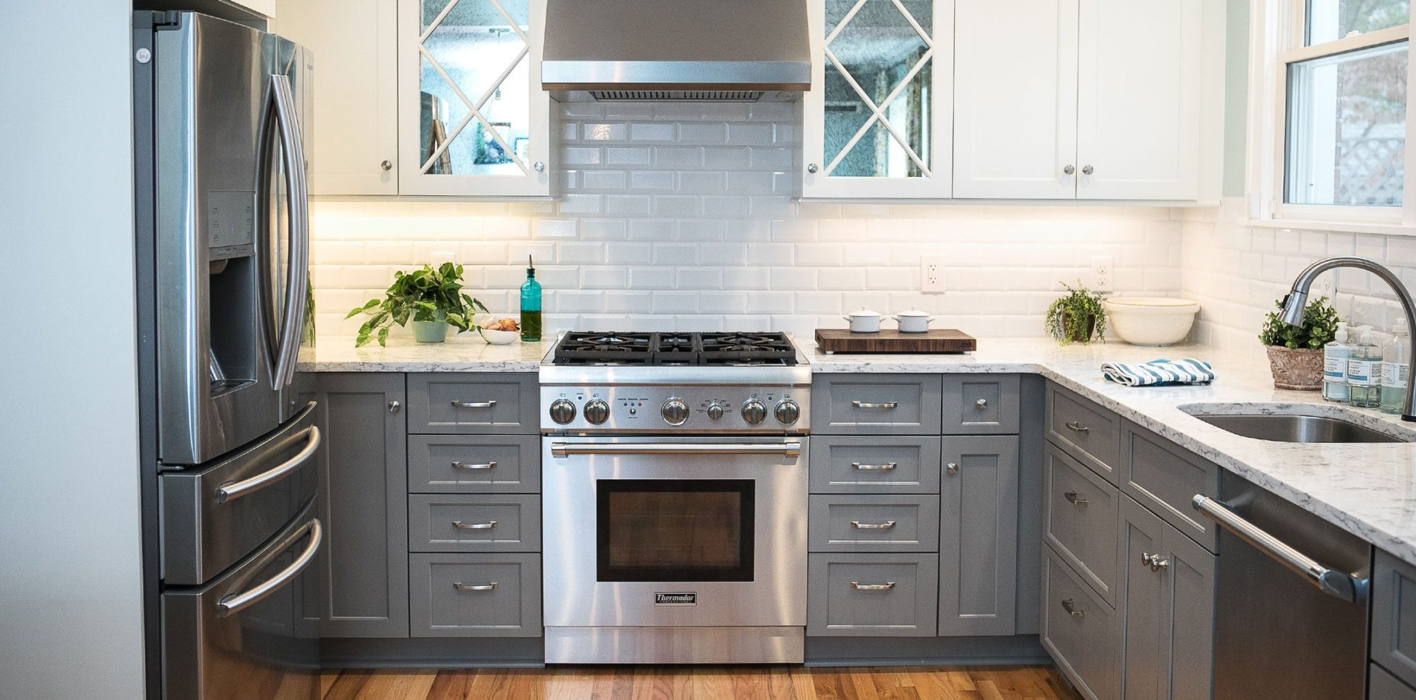 Crisp gray drawers against white mirrored cabinets in renovated kitchen