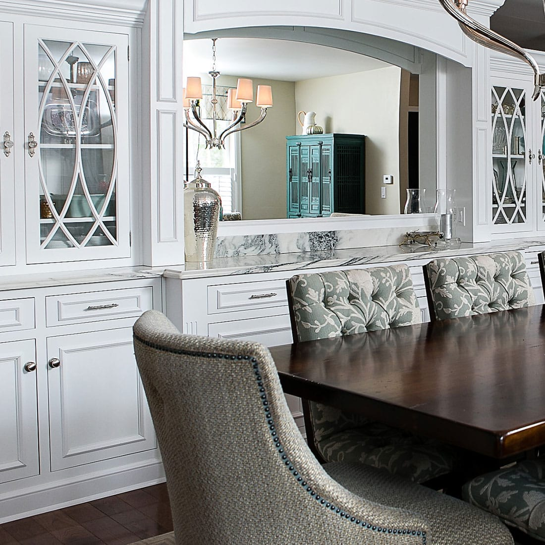 marble buffet behind cushioned chairs around large dining table