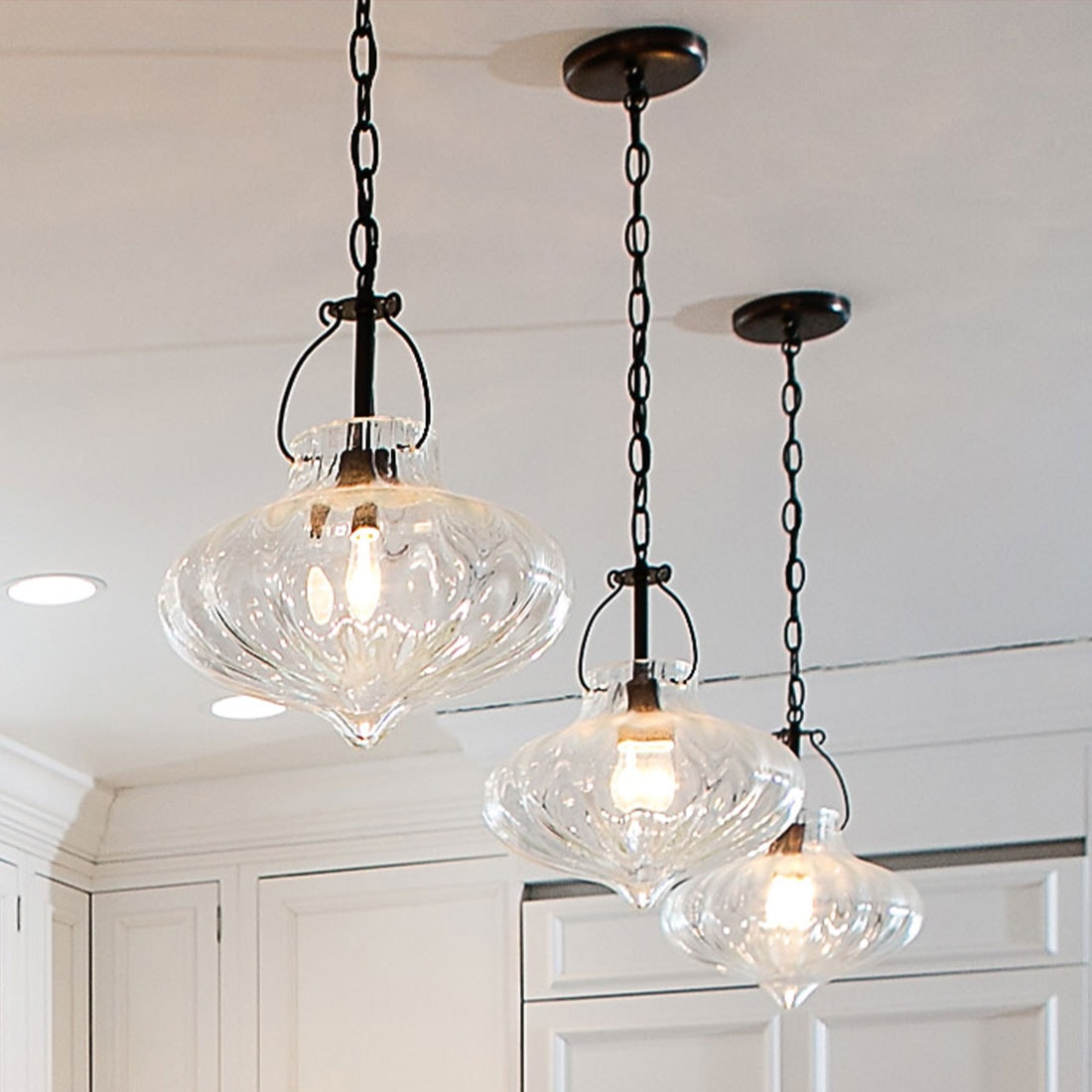 three bulb clear glass pendant lights in renovated kitchen
