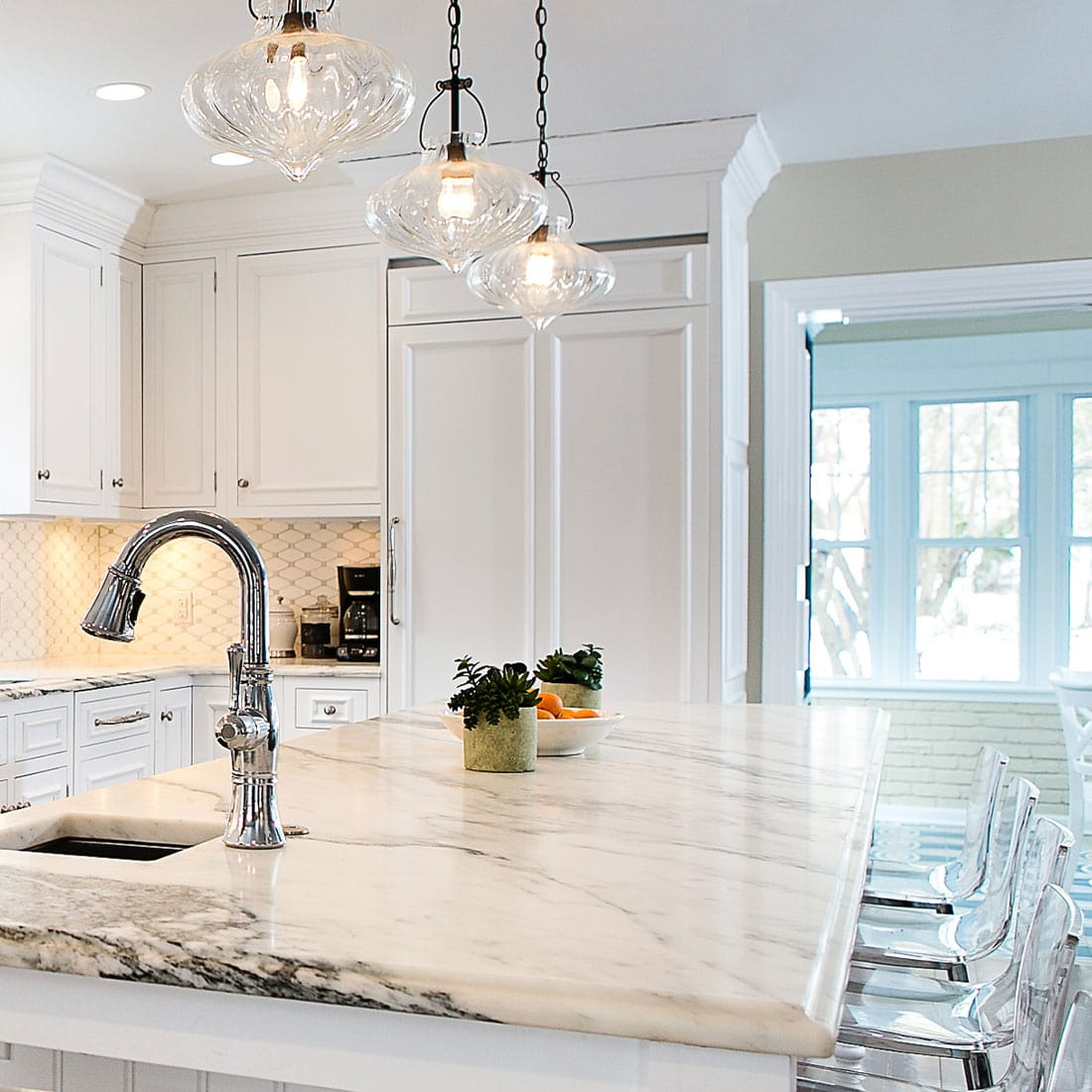 Chrome finishes with white marble island in renovated kitchen