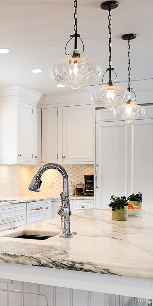 White marble countertops on island in renovated kitchen