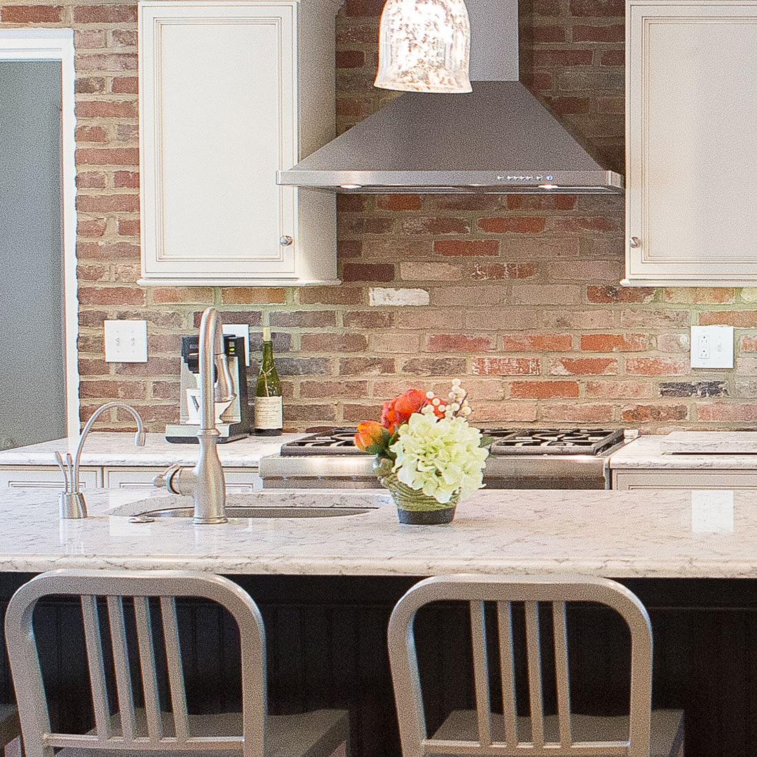 modern range with minimal back against brick backsplash in renovated kitchen