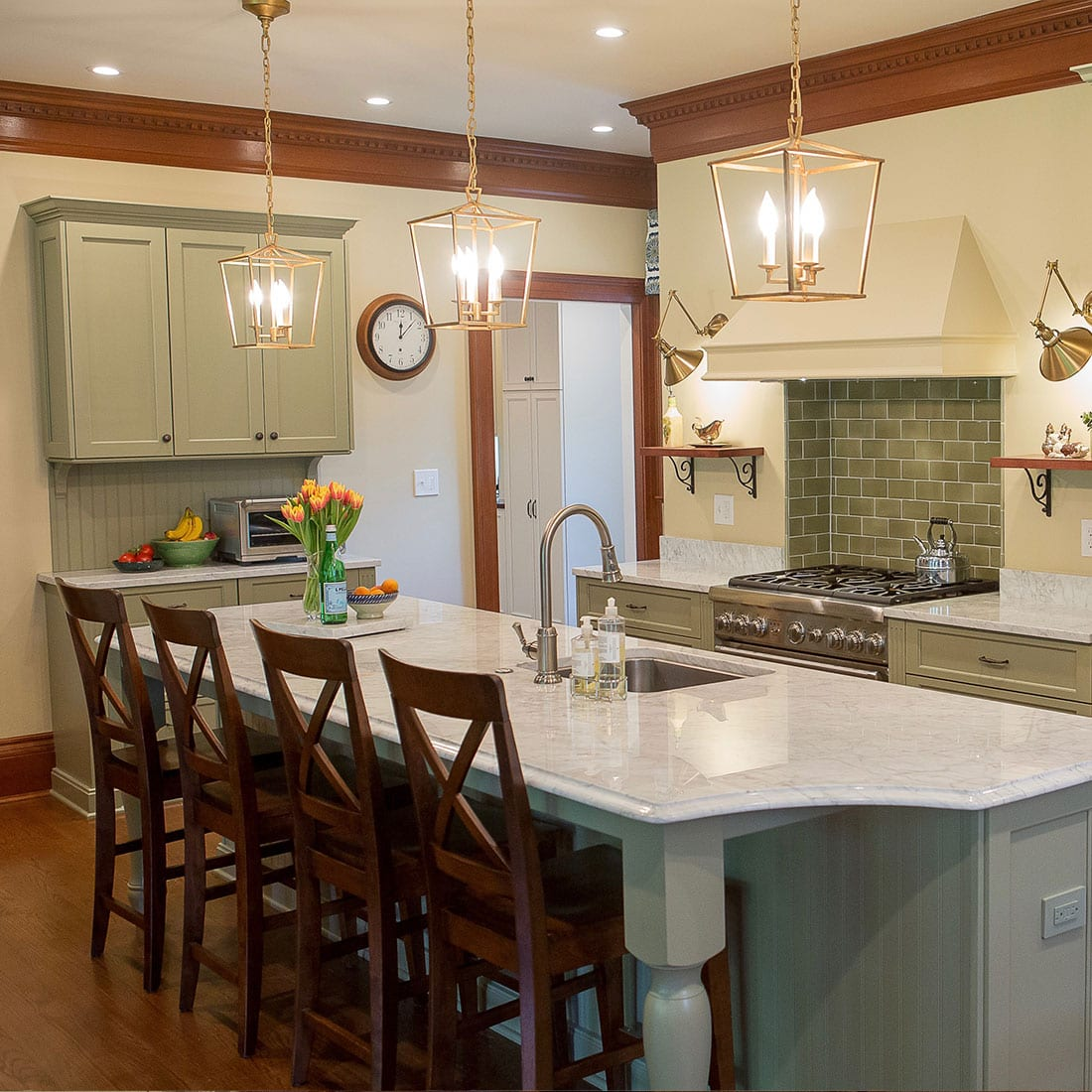 Pops of green accent warm kitchen with brass pendant lights