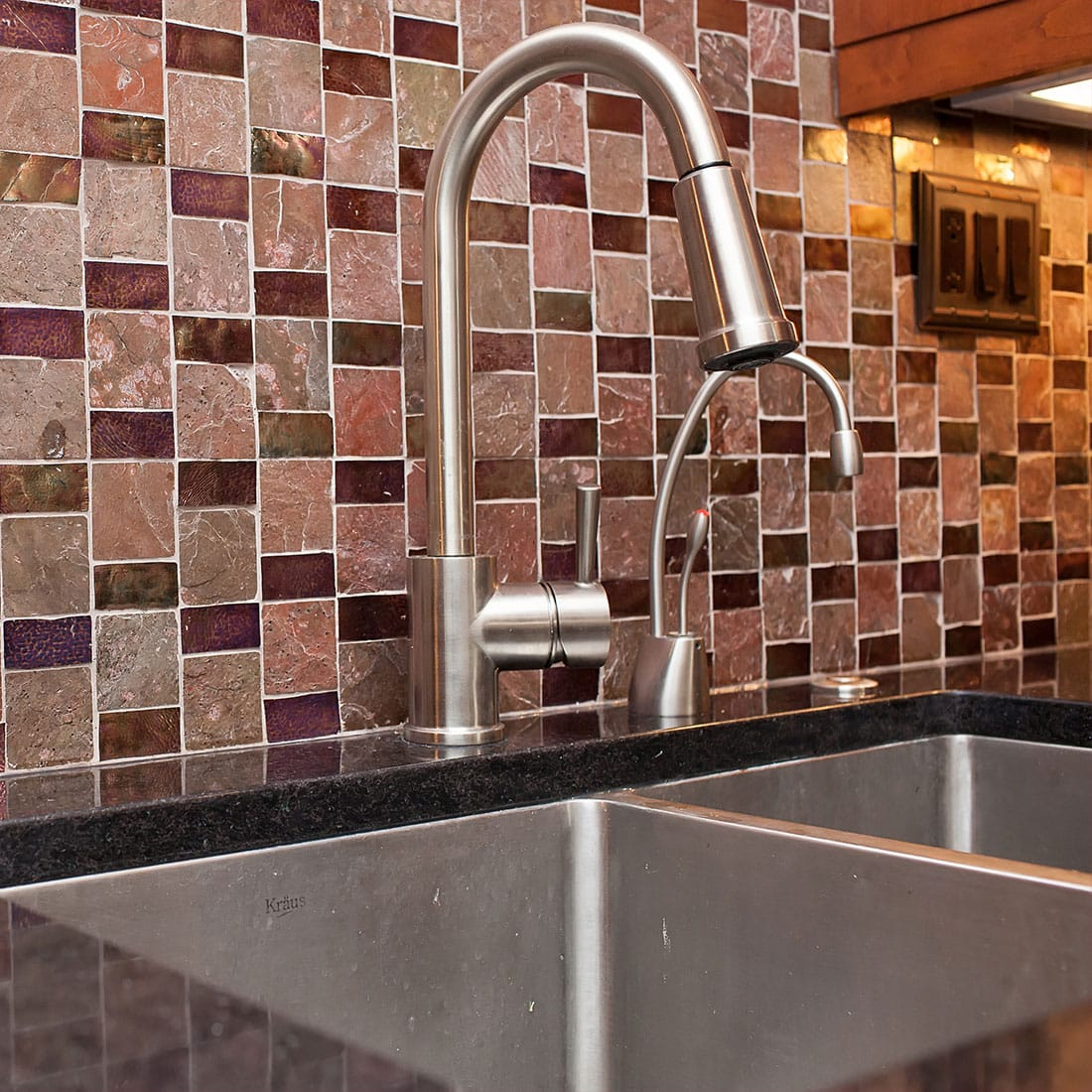 Custom maroon tile backsplash against black marble in renovated kitchen