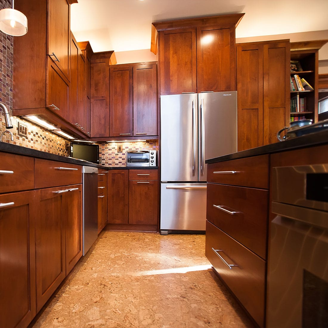 Warm wood cabinets with bamboo floors and stainless steel appliances and hardware in renovated kitchen