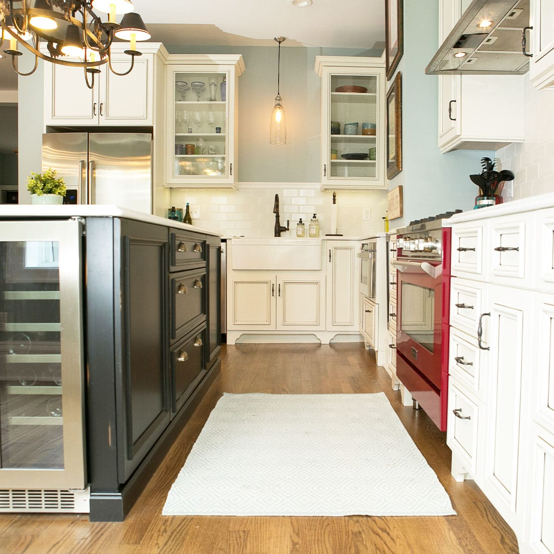 Contrasting island in white kitchen with red oven in renovated kitchen