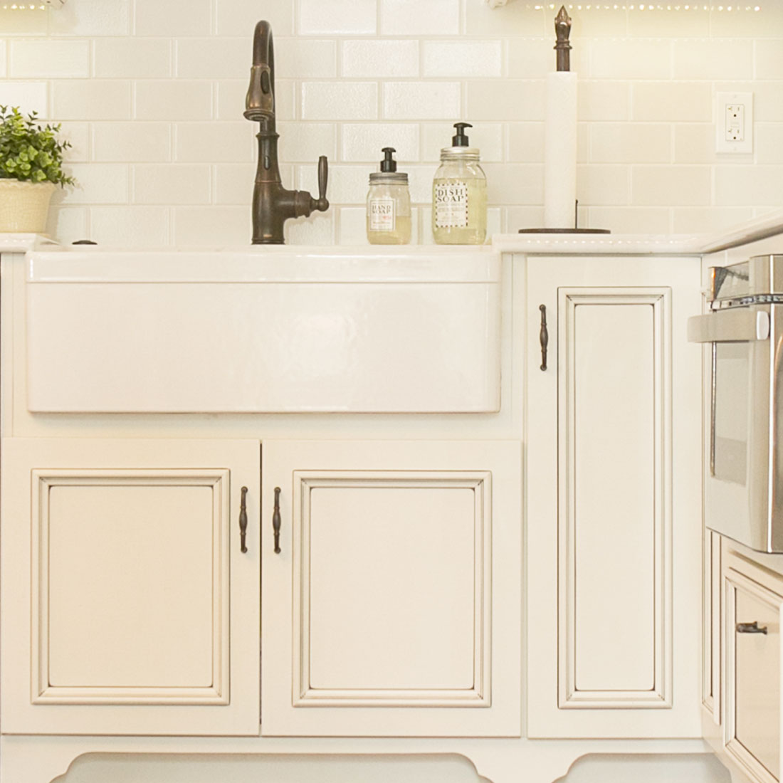 White detailed kitchen cabinets around a farmhouse sink with oil rubbed bronze faucet