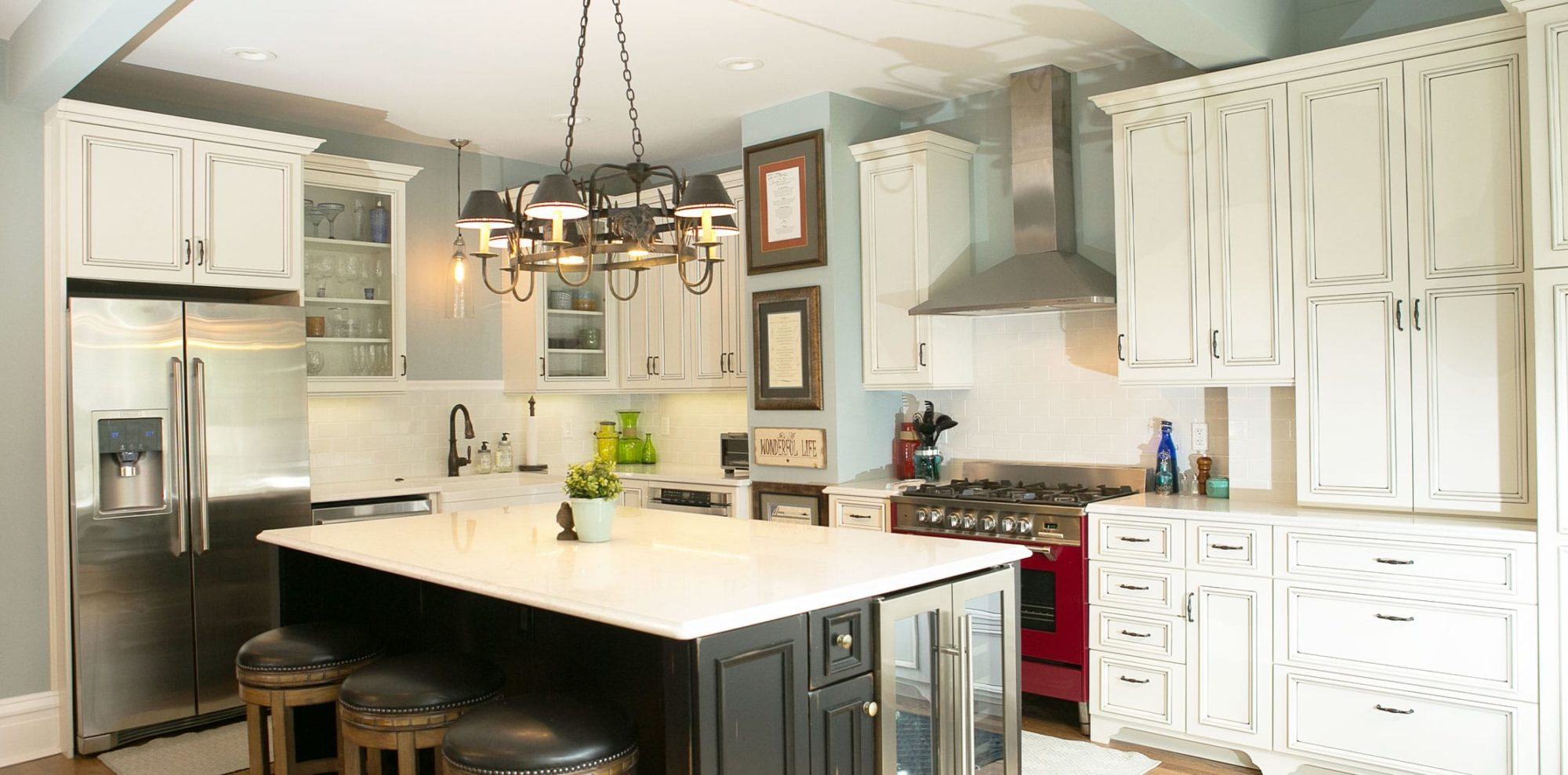 Ornate white kitchen cabinets with contrasting island in modern renovated kitchen