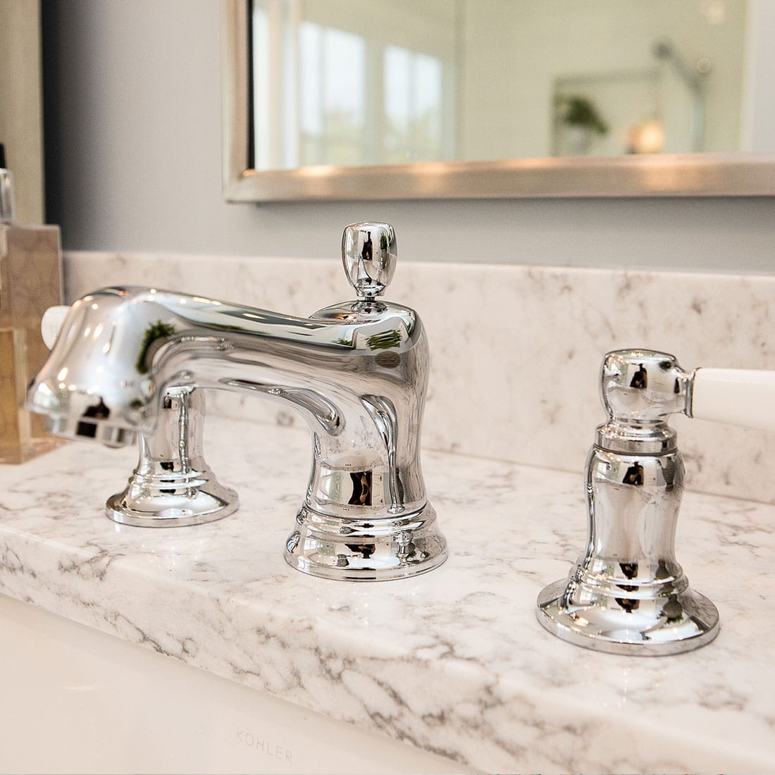 Modern chrome faucet on white marble counter in renovated bath