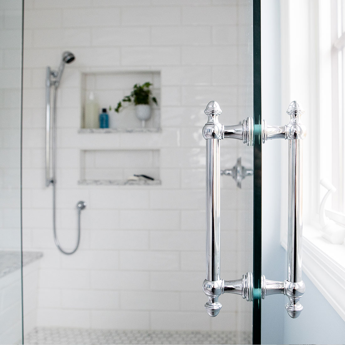 Chrome handle on glass shower enclosure in renovated bath