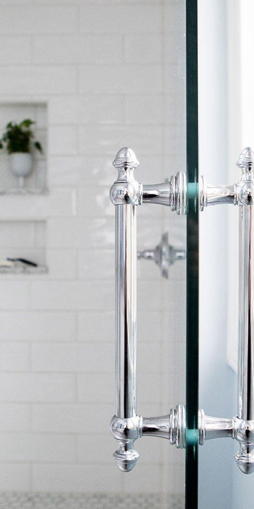 Sleek chrome handle on glass door in renovated bath