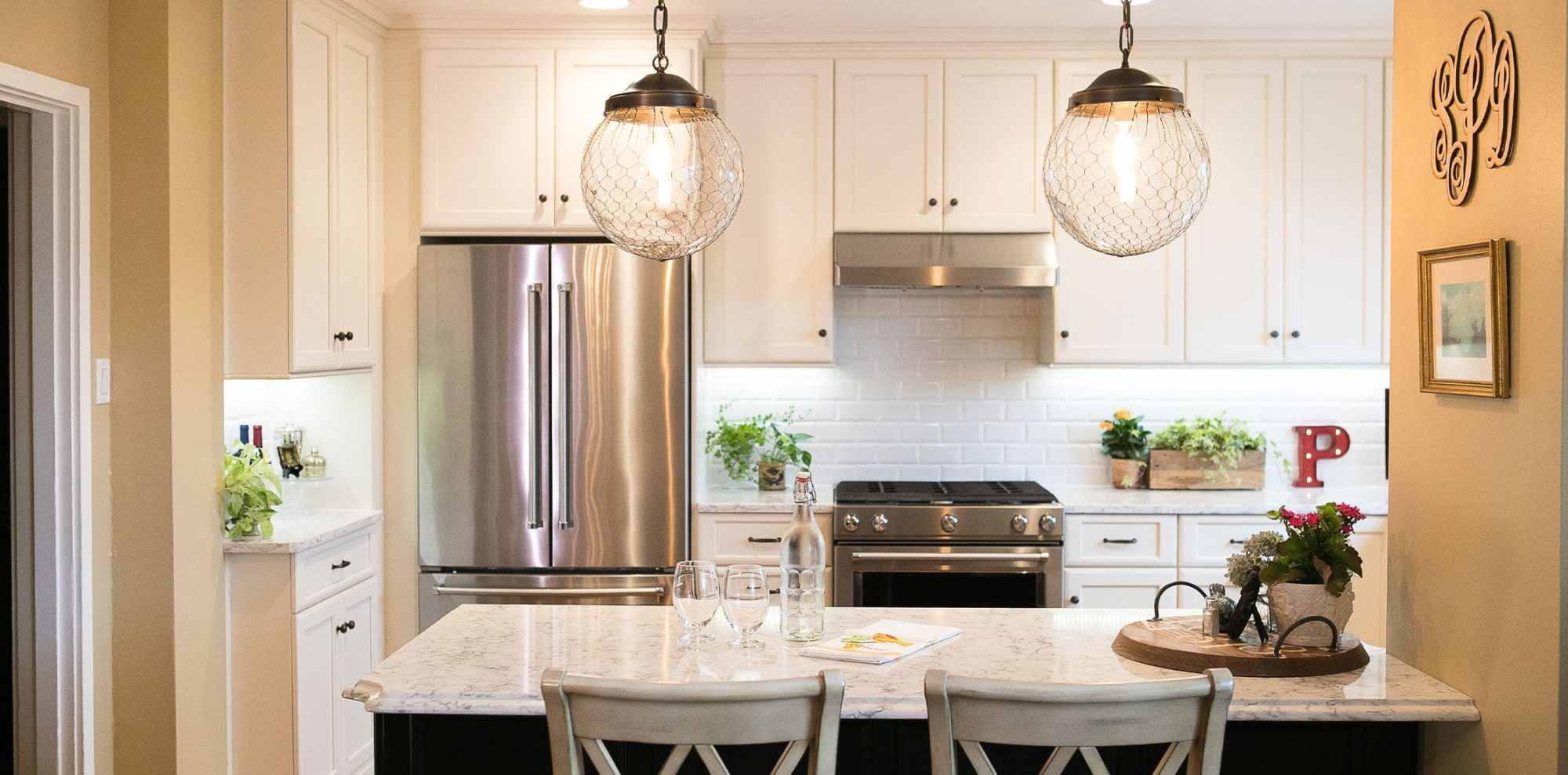 large globe pendant lights over marble seating area in renovated kitchen